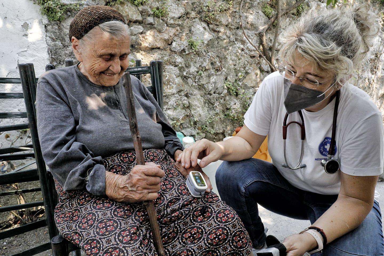 Eine Ärzte der Welt-Mitarbeiterin untersucht eine ältere Patientin. Foto: Yiannis Yiannakopolous