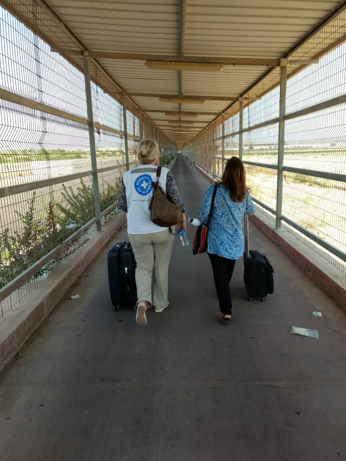 Ärzte der Welt Mitarbeiterinnen gehen durch einen 800 Meter langen, käfigartigen Gang. Die Einreise in den Gazastreifen steht unter strengsten Bedingungen - Pässe werden an beiden Enden des Korridors kontrolliert.