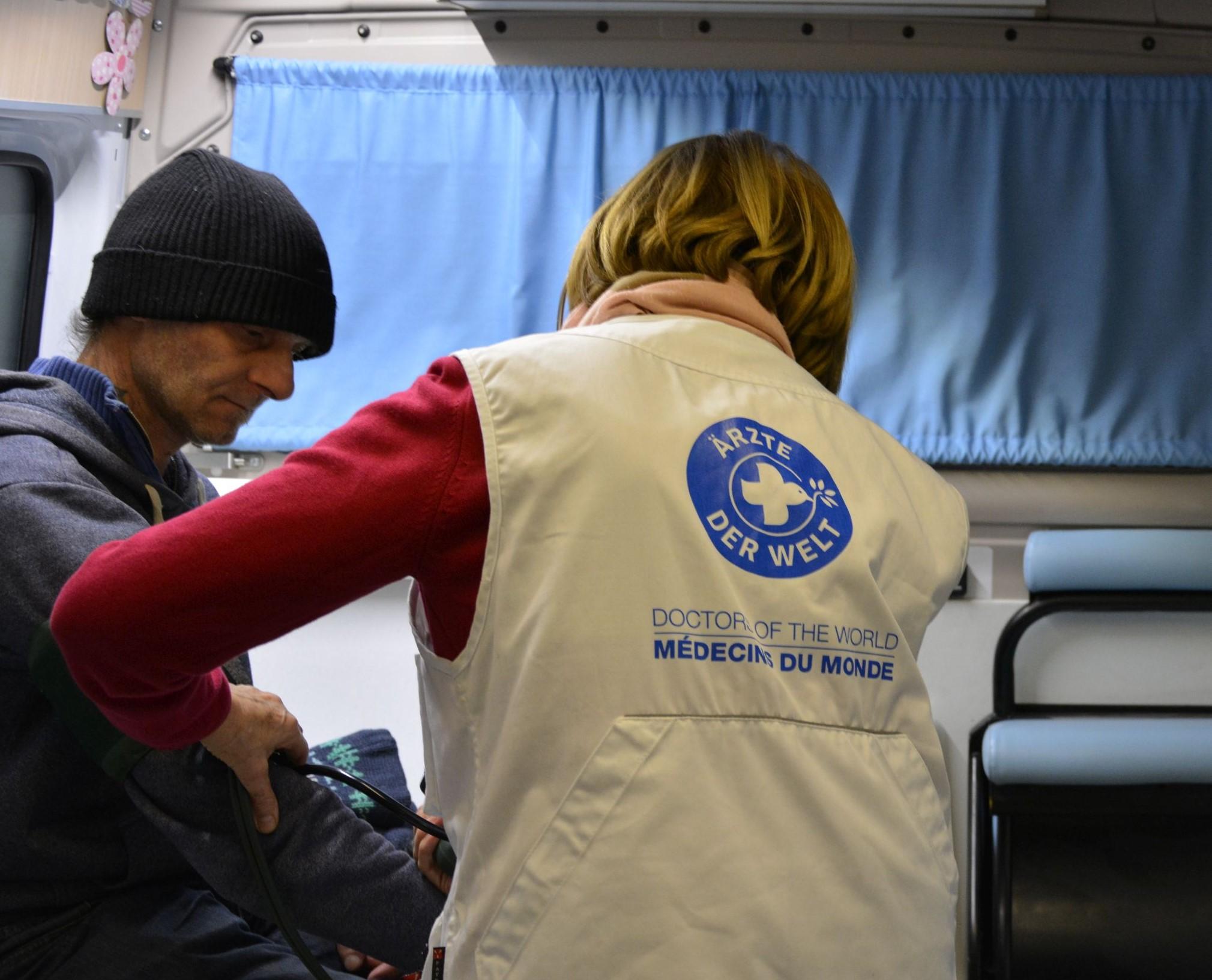 Eine ehrenamtliche Ärztin behandelt einen Patienten im Behandlungsbus. Foto: Ärzte der Welt