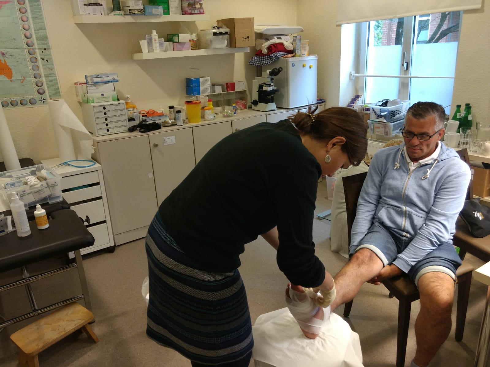 Ein Patient, der wegen eines schlecht eingestellten Diabetes einen Zeh verloren hat, wird von der Ärztin versorgt.