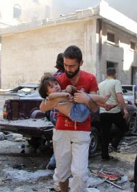 Ein Vater trägt sein verletztes Kind, Syrien. Foto: Omar Haj Kadour, AFP
