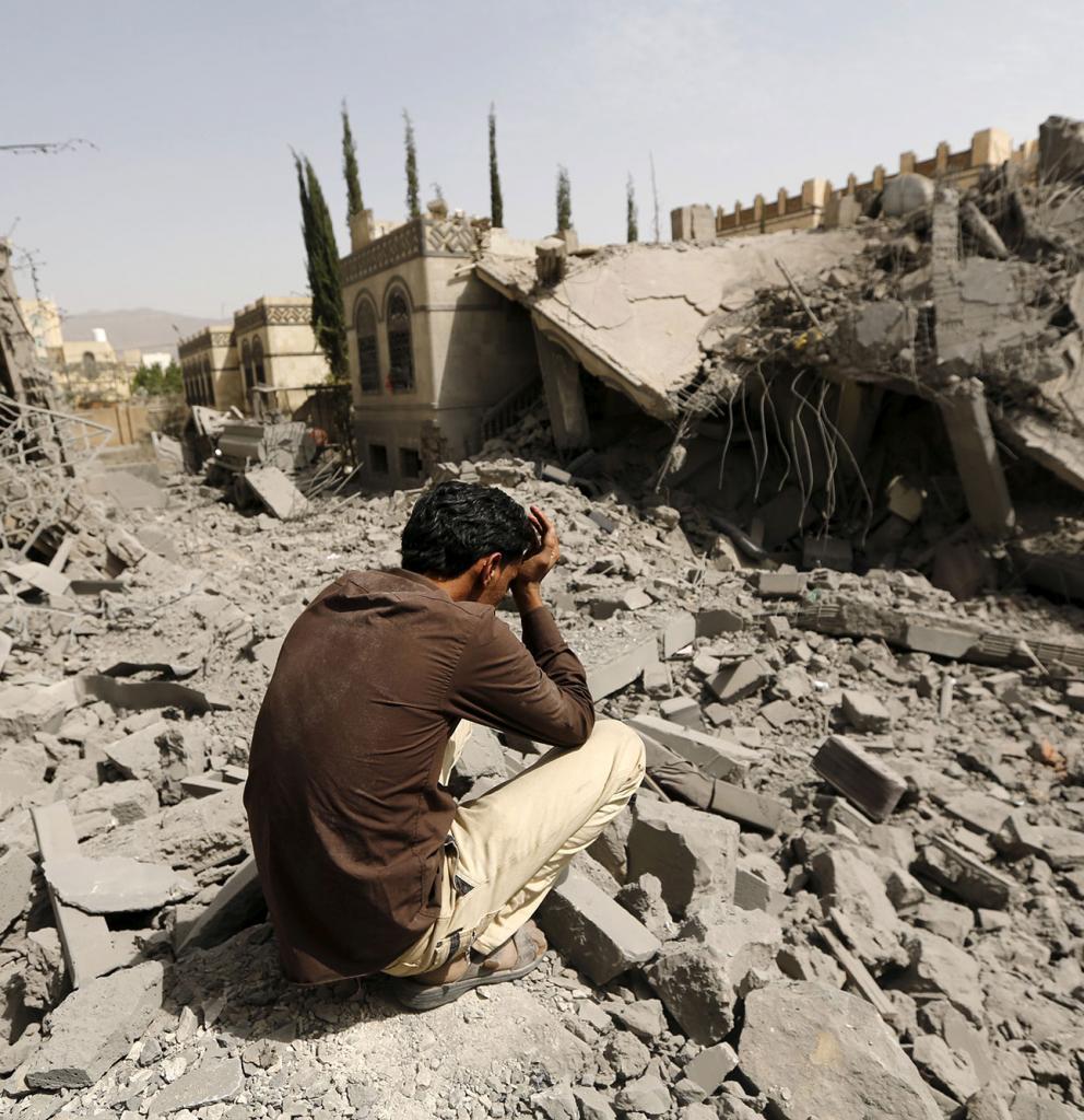 Ein Mann sitzt zwischen Trümmern im Jemen