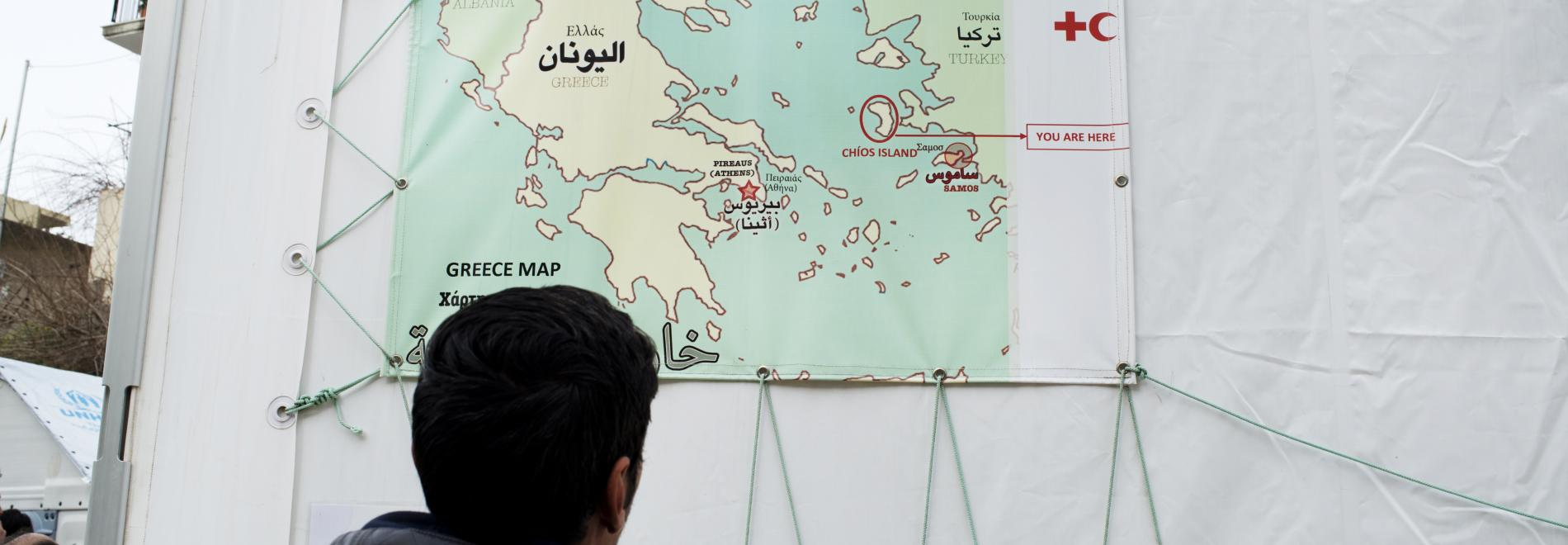 Ein Flüchtling betrachtet eine Karte von Griechenland