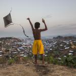 Ein junge spielt mit seinem Drachen in einem Flüchtlingscamp, Bangladesch. Foto: A. Finistre