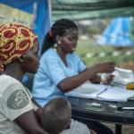 In einem provisorischen Zeltlager lässt eine Frau Ihr Kind von der pädiatrischen Fachkraft des Ärzte der Welt-Teams untersuchen. Mosambik. Foto: Czuko Williams