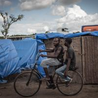 Männer fahren Rad in einem Flüchtlingslager in Mosambik