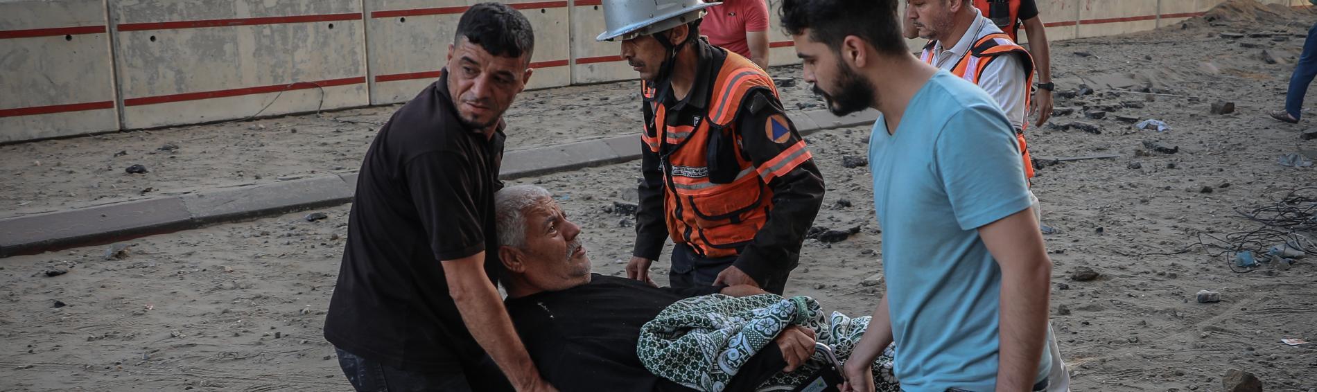 Nachbarn und Rettiungskräfte evakuieren einen alten und behinderten Mann aus dem Gebiet in Gaza-Stadt, das beschossen wurde. Foto: Motaz Azaiza