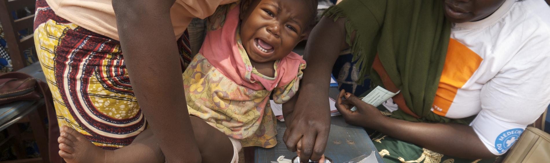 Ein Kind wird von einem Helfer untersucht. Foto: Christophe Garcot