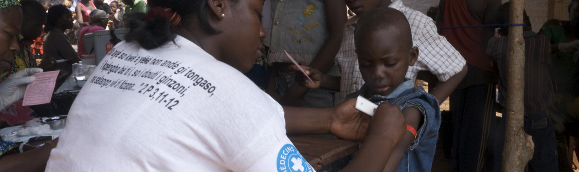 Eine Helferin untersucht einen Jungen mithilfe des MUAC-Bandes zur Feststellung von Mangelernährung. Foto: Christophe Garcot