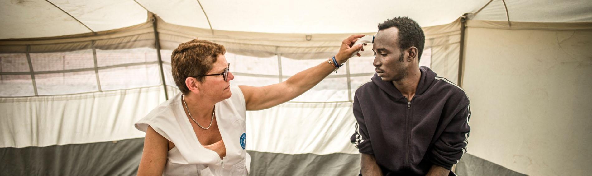 Eine ehrenamtliche Ärztin behandelt einen Migranten in Calais. Foto: Olivier Papegnies