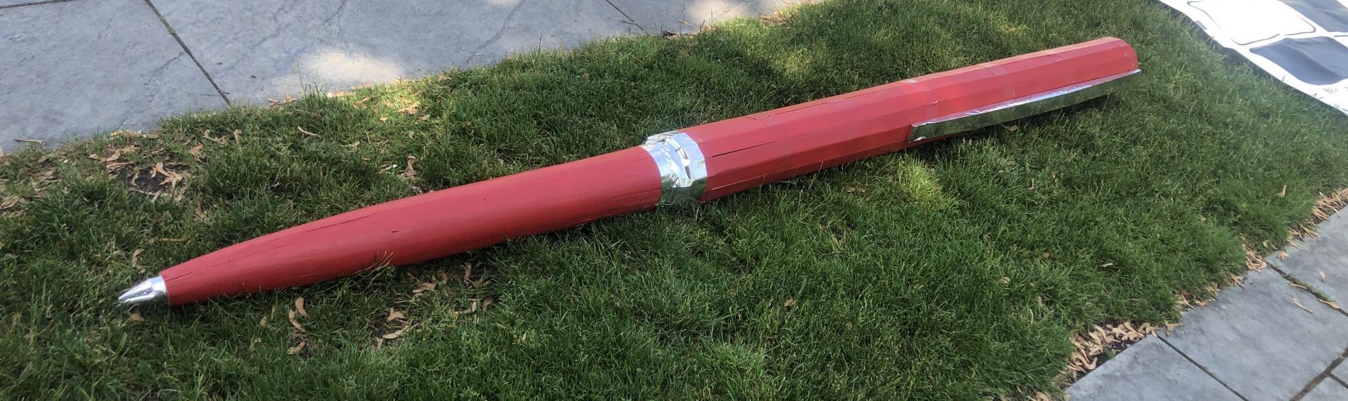 Ein großer roter Kugelschreiber liegt auf einem Stück Rasen vor dem Kanzleramt