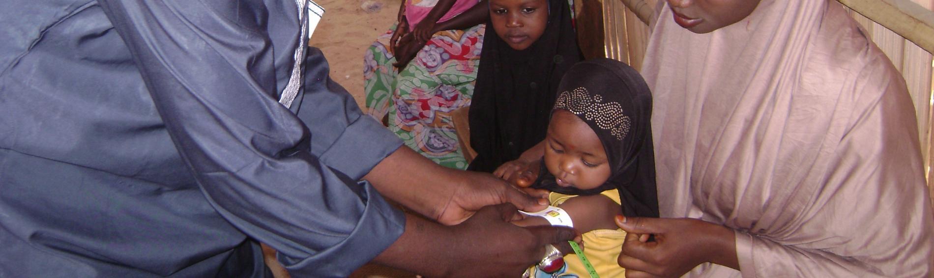 Ein Mitarbeiter von Ärzte der Welt untersucht ein nigerianisches Kind.