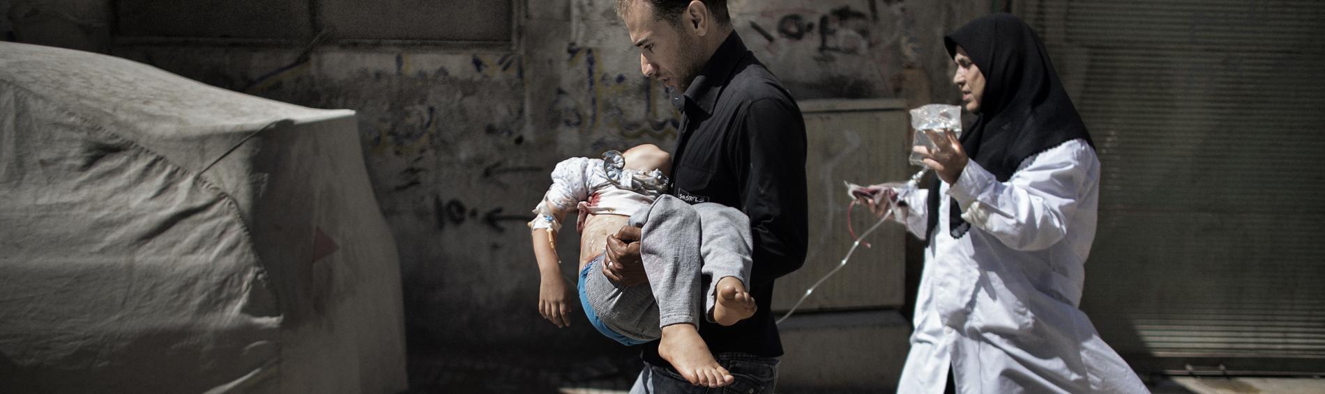 Ein Vater trägt sein Kind, das bei einem Bombenangriff verletzt wurde. Foto: Marco Longari, AFP