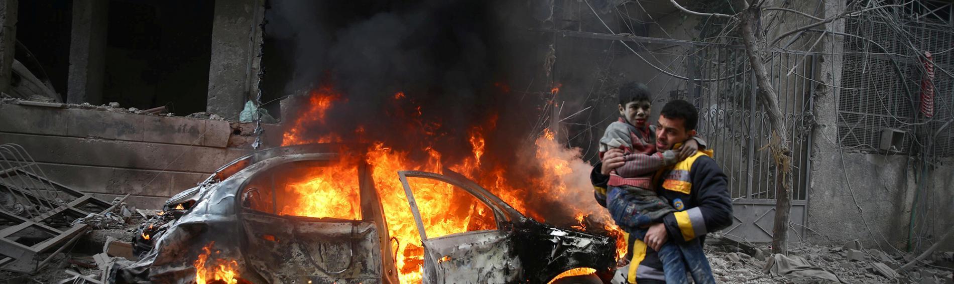 Ein Mann mit einem Kind auf dem Arm vor einem brennenden Auto