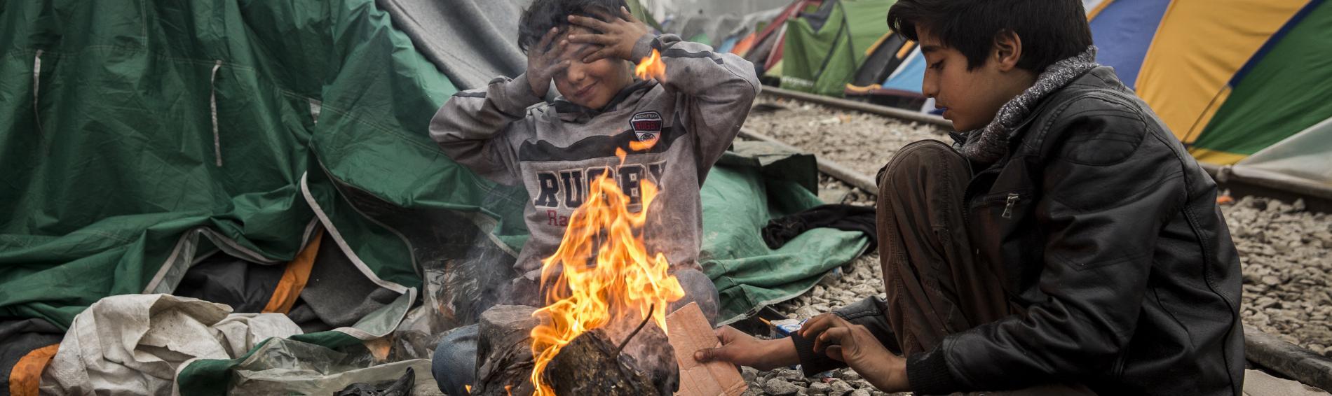 Zwei Kinder wärmen sich im griechischen Flüchtlingscamp Idomeni an einem offenen Feuer. Foto: Olmo Calvo