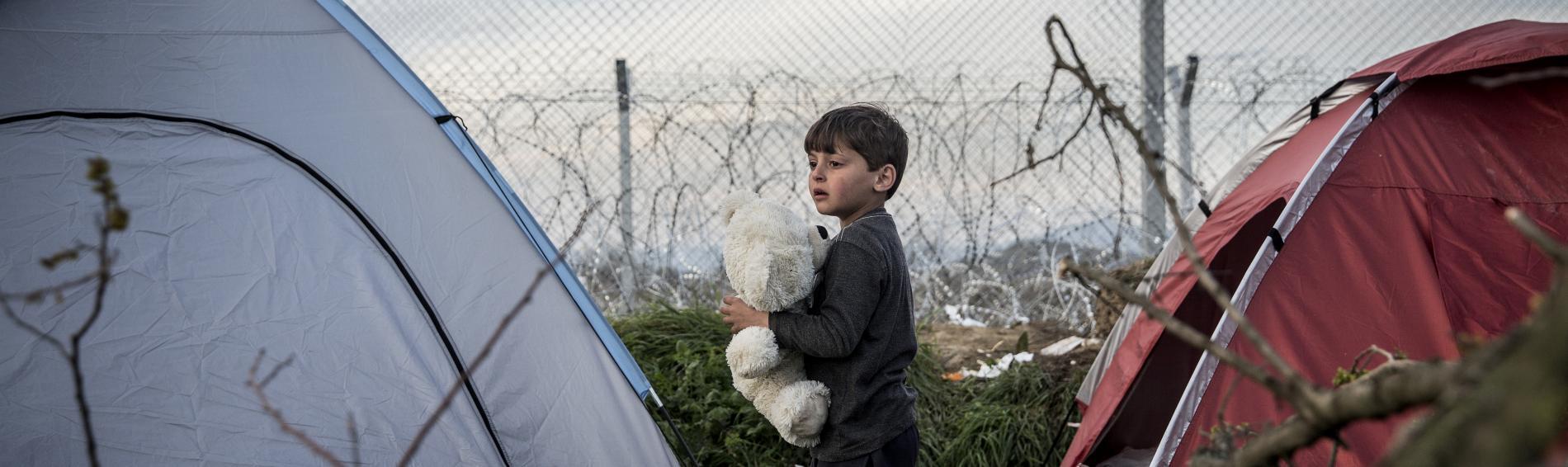 Ein Flüchtlingskind schläft im Freien