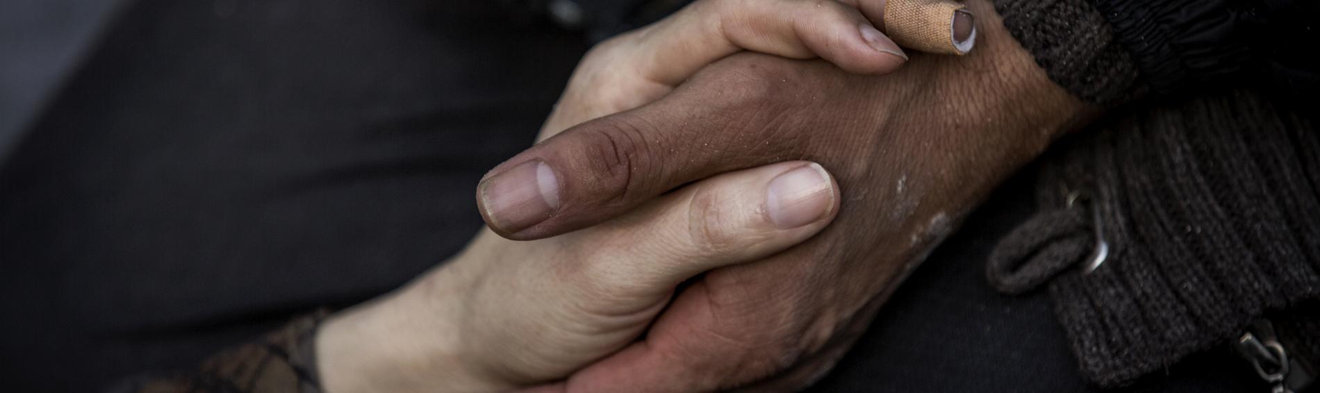 Zwei Hände greifen ineinander. Foto: Olmo Calvo