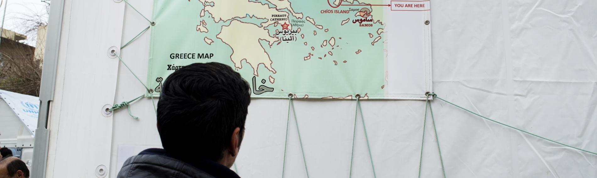 Ein Flüchtling betrachtet eine Landkarte, auf der die Insel Chios markiert ist.
