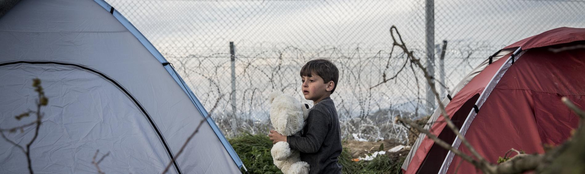 Kind zwischen Zelten am Grenzzaun zwischen Griechenland und Mazedonien (FYROM)