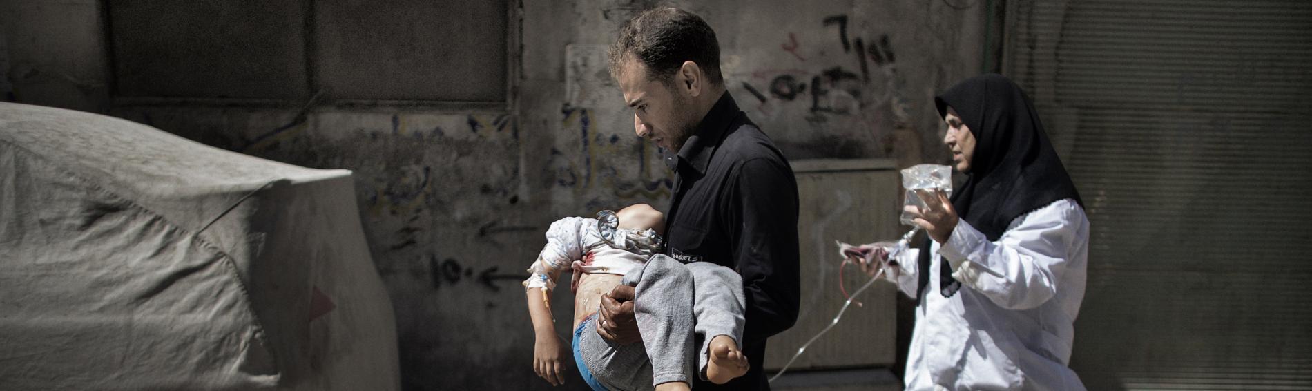 Ein Mann trägt seine verletzte Tochter in ein Krankenhaus in Aleppo. Foto: AFP Photos